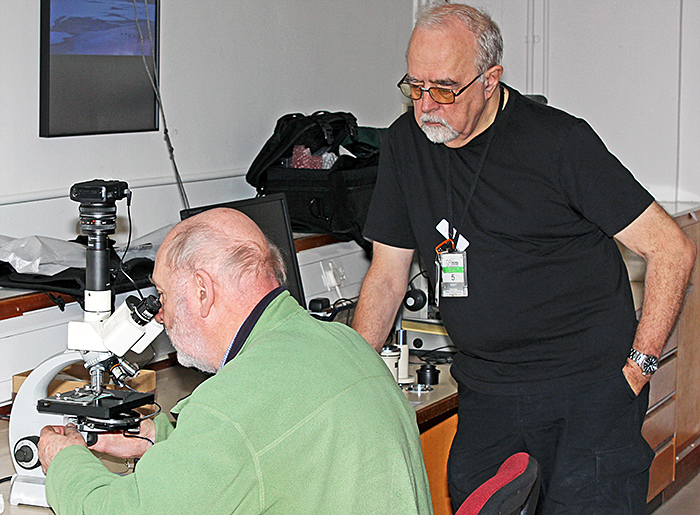 Paul Smith watching David Linstead adjusting a Zeiss Standard microscope