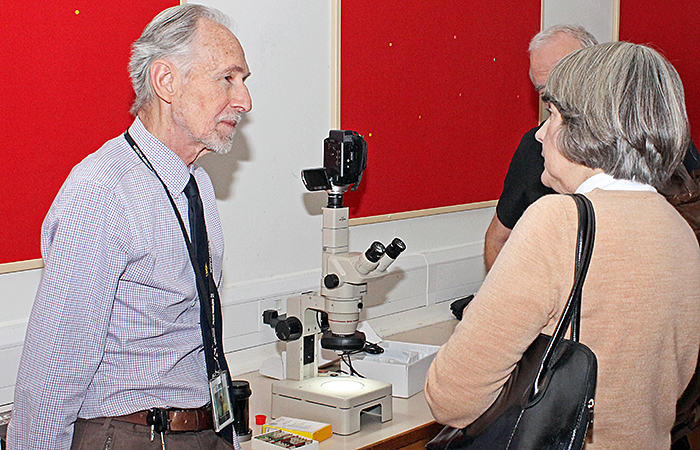 Dennis Fullwood discussing his stereomicroscope with a visitor