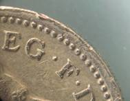 Dots around obverse of £1 coin