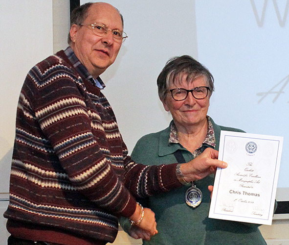 Chris Thomas receiving his artwork certificate from Joan Bingley
