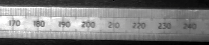 Doubled image of a steel ruler through stressed polycarbonate sheet